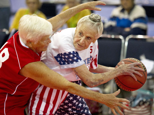 Two older ladies playing basketball
